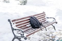 A forgotten backpack on an old, snowy bench in the park stock photo
