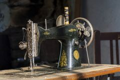 Forgotten black retro sewing machine in abandoned old house. Royalty Free Stock Photos