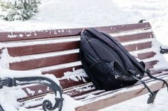 Forgotten black, sports backpack on an old bench in the park in the winter stock images