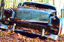 Forgotten Car with Autumn Leaves. A junk car is abandoned in the forest and covered with autumn leaves Royalty Free Stock Image