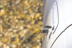 Forgotten car keys in the door, a background of a blurry autumn forest with a bokeh effect royalty free stock photography