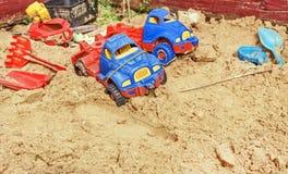 Forgotten cars in sandbox. Forgotten of childhood cars in sandbox at summer day Royalty Free Stock Photos