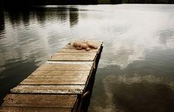 Forgotten doll on a wooden mooring Royalty Free Stock Images