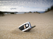 Forgotten mobile phone on the beach. And over the sand Stock Photo