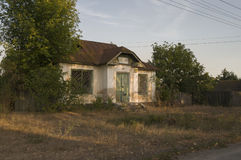 Forgotten old building in little suburb. Early fall trees of green and tint of yellow colors.  Stock Photo