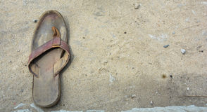 The forgotten one. A brown forgotten old and aged slippers. commonly known as palm slippers in Nigeria. Abandoned with it other leg missing Stock Image