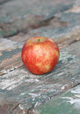 Forgotten red apple on a wooden table Royalty Free Stock Photo