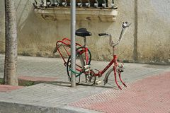 Forgotten red bicycle attached to street pillar with lock stands without wheels on the street of Calella royalty free stock image