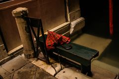Forgotten Red Umbrella on a Green Bench in Venice royalty free stock photos
