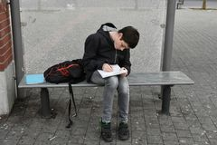 Forgotten school homework. Boy makes forgotten homework in the morning at the school bus stop Stock Photo