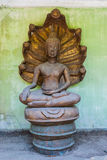 Forgotten smiling Naga head covered Buddha image (Nak Prok Image) Royalty Free Stock Images