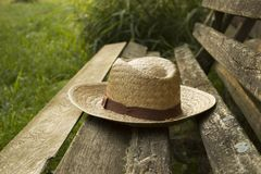 A forgotten straw hat on an old village bench on a warm sunny day in the nature in a village on a background of green grass stock photography