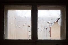 Fori di pallottola sul vetro di finestra rotto fotografia stock