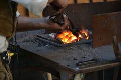 Forjador negro que calienta para arriba un hierro foto de archivo libre de regalías