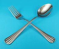 Fork. And spoon on blue background stock photography