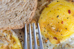 A fork aiming at fried eggs and toast with seasoning stock image