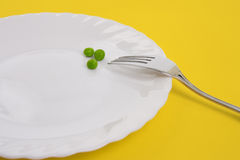 Fork approaching peas on white plate. Photo of three green peas on a white plate isolated on yellow background Royalty Free Stock Photography