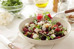 Fork with beetroot salad and the plate on white wooden table. Healthy food for diet Stock Photo