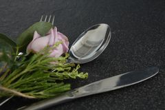 Fork and butter knife with flower on black background. Close-up of fork and butter knife with flower on black background Stock Photography