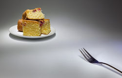 Fork and cakes. Metal fork in one corner and some cakes on white plate in other corner Stock Photos