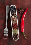 Fork chili pepper and spice. Mix on brown wood board Royalty Free Stock Photos
