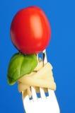 Fork con las pastas, la albahaca y el tomate Imagen de archivo libre de regalías