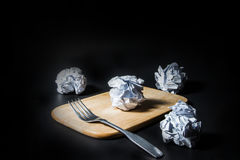 Fork and crumpled paper on black background. Royalty Free Stock Photo