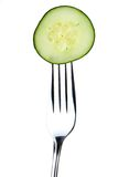 Fork and cucumber. Metal fork and green fresh cucumber on it Stock Image