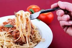 Fork de la explotación agrícola de la mano con espagueti en una placa Imágenes de archivo libres de regalías