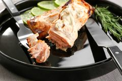 Fork with delicious cooked salmon on plate. Closeup Stock Image