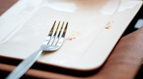 Fork on empty dish. Fork on empty white dish after finish bakery Royalty Free Stock Photos