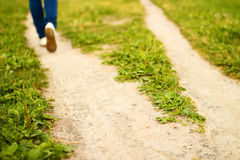 Fork of footpath and feet of going person Stock Images