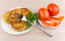 Fork on fried cutlets, red tomatoes and dill on table Stock Photos