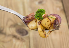 Fork with fried Potatoes on wood Royalty Free Stock Photos