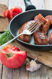 Fork and fried sausage in a skillet. Royalty Free Stock Photography