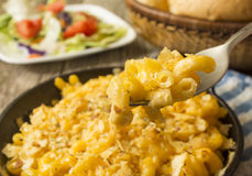 Fork full of cheese. Pan of baked macaroni and cheese in a skillet served with salad and roll royalty free stock photos
