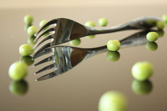 Fork with green peas. Fork lying on the table surrounded by green peas with a reflection Stock Image