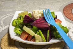 Fork and green salad. In a plate on the table royalty free stock image
