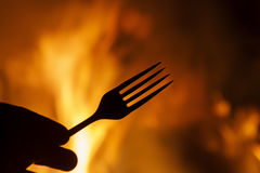 Fork in hand against a background of fire Royalty Free Stock Photography