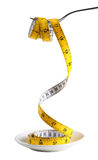 A fork holding a measuring tape from a plate Royalty Free Stock Photos
