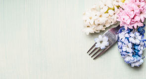 Fork with hyacinths flowers on light green background, top view, banner for website or placard.  Place setting concept. Stock Image