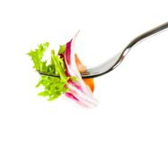 Fork with italian fresh salad on top on white Stock Photo