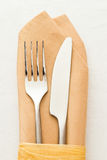 Fork and knife. On beige napkin stock images