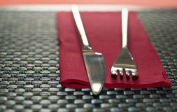 Fork and knife. A Fork and a knife over a napkin in a restaurat table. Shallow DOF Royalty Free Stock Image