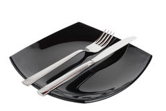 Fork & knife on a black plate Royalty Free Stock Photo