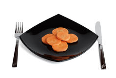 Fork, knife, black plate and carrot. Three. Royalty Free Stock Photography