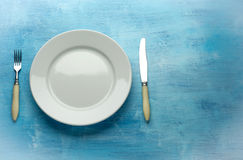 Fork with knife and blank plates. On wooden table Royalty Free Stock Images