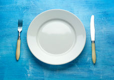 Fork with knife and blank plates. On wooden table Stock Images