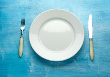 Fork with knife and blank plates. On wooden table Royalty Free Stock Image