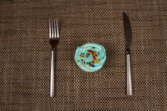 Fork, knife and a blue cupcake with cream. Breakfast sweet tooth. Denim, shiny cutlery, fresh cupcake with blue cream and confectionery Topping Stock Photos